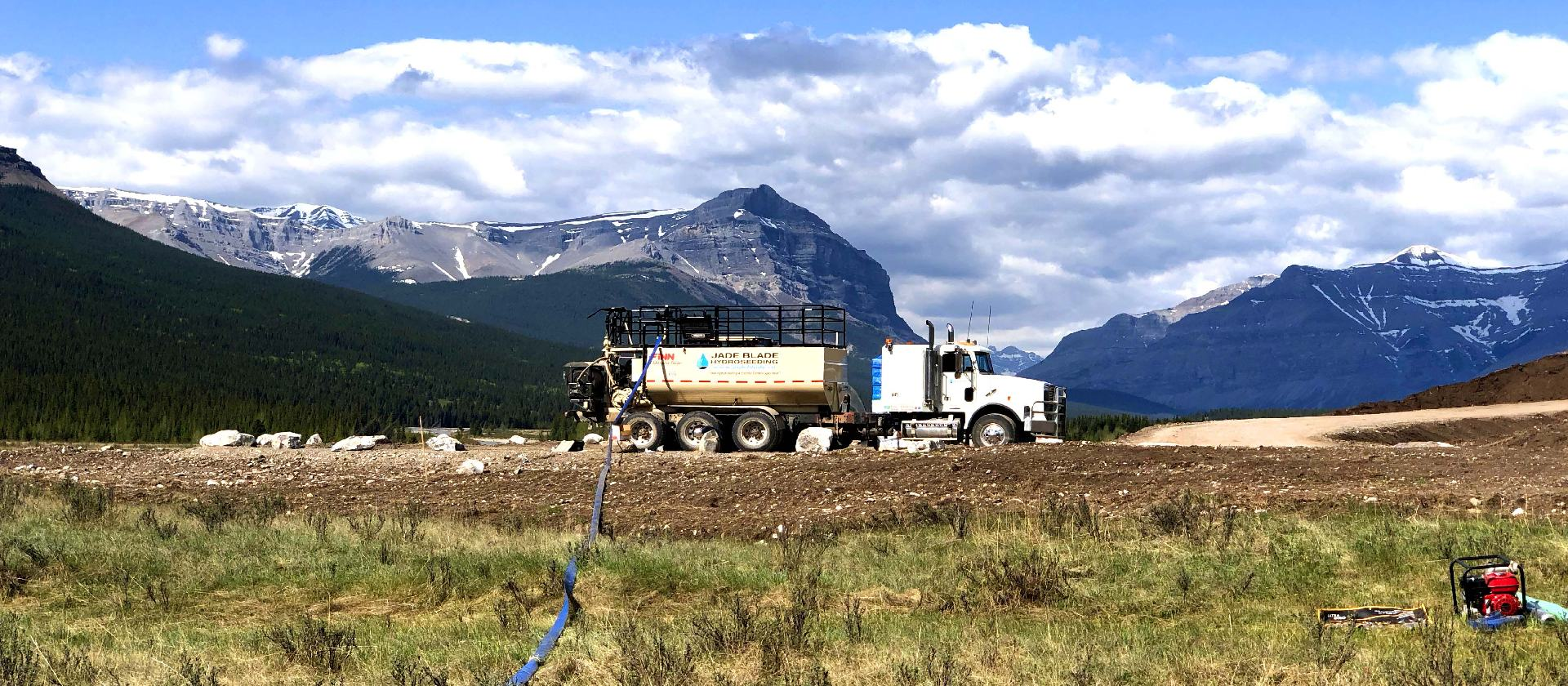 jade blade hydroseeding truck and hose in front of moutains